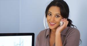 Mexicaanse bedrijfsvrouw die bij cellphone en het glimlachen spreekt Royalty-vrije Stock Afbeeldingen
