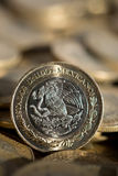 Mexicaanse munt in de voorgrond, met veel meer muntstukken op de achtergrond Stock Foto's