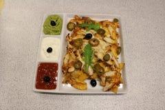 Mexicaanse nachos met kip Nachos met graanspaanders, kaas, salsa, guacamole, zure room, en kip Een plaat van tortillanachos stock afbeelding