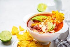 Mexicaanse soep Chili con carne met bonen, kip, graan en nachos in witte kommen - traditioneel Mexicaans voedsel stock foto