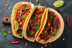 Mexicaanse taco's met rundvlees, groenten en salsa Taco'sal predikant op houten raad op zwarte achtergrond Hoogste mening stock fotografie