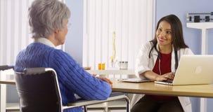 Mexicaanse vrouw arts die met bejaarde patiënt spreken Stock Afbeeldingen
