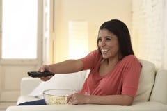 Mexicaanse vrouw het letten op televisie bij banklaag gelukkige opgewekte het genieten van romantische film stock foto