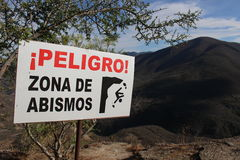 Mexican Abyss. A warning sign next to a cliff at Hierve el agua in the State of Oaxaca, Mexico Royalty Free Stock Image