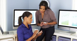 Mexican and African American business women using mobile phones and working together Royalty Free Stock Photos