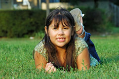 Mexican-American Girl. Cute Mexican girl lying on green grass Royalty Free Stock Image