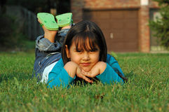 Mexican-American Girl. Cute Mexican girl lying on green grass Stock Photo