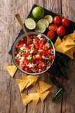 Mexican appetizer Pico de Gallo close-up in a bowl. Vertical top. Mexican appetizer Pico de Gallo close-up in a bowl on the table. Vertical top view from above stock photography
