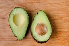 Avocado halves. Mexican avocado halves on wood background Royalty Free Stock Photo