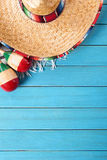 Mexico, Mexican sombrero wood background vertical copy space. Mexican sombrero and maracas with traditional serape blanket laid on an old blue painted pine wood Royalty Free Stock Photography