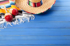 Mexico, Mexican background sombrero blanket wood copy space. Mexican sombrero and maracas with traditional serape blanket laid on an old blue painted pine wood Royalty Free Stock Image