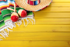 Mexico, Mexican wood background sombrero copy space. Mexican sombrero, maracas and traditional serape blanket laid on a yellow painted pine wood floor royalty free stock photos