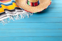 Mexico, Mexican sombrero background copy space. Mexican sombrero and traditional serape blanket laid on an old blue painted pine wood floor. Space for copy stock photography
