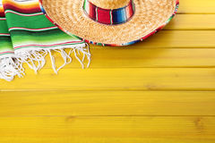 Mexico, Mexican sombrero blanket, wood background copy space. Mexican sombrero and traditional serape blanket laid on a yellow painted pine wood floor.  Space Stock Photography