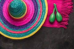Mexican background with sombrero, blankets and maracas. Mexican background. Sombrero, maracas and blankets on rustic slate background. Top view with copy space stock photography