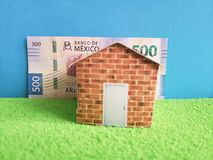 Mexican banknote, figure of a house on green surface and blue background. Backdrop for mortgage and housing value ads, loan for home construction and remodeling royalty free stock photo