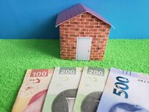 Mexican banknotes, figure of a house on green surface and blue background. Backdrop for mortgage and housing value ads, loan for home construction and remodeling royalty free stock images