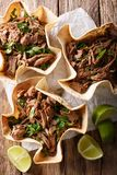 Mexican barbacoa tacos with spicy pulled beef close-up. Vertical. Mexican barbacoa tacos with spicy pulled beef close-up on the table. Vertical top view from stock photo