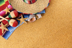 Mexican sombrero, beach background, copy space. Mexican beach background with sombrero straw hat, traditional serape blanket, starfish, seashells and maracas Stock Photos