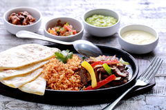 Mexican beef fajitas with four different sauces. Mexican beef fajitas served with rice, soft flour tortillas at hot plate and four different sauces Royalty Free Stock Photos