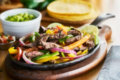 Mexican beef fajitas in iron skillet with bell peppers and guacamole on the side royalty free stock photo