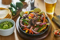 Mexican beef fajitas in iron skillet with guacamole and beer royalty free stock photos