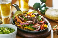 Mexican beef fajitas in iron skillet with guacamole and beer royalty free stock image
