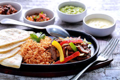 Mexican beef fajitas. Served with rice, soft flour tortillas at hot plate and four different sauces Royalty Free Stock Photo