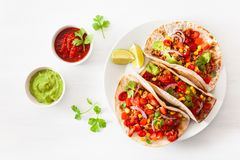 Mexican beef and pork tacos with salsa, guacamole and vegetables royalty free stock images
