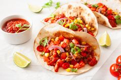 Mexican beef and pork tacos with salsa, guacamole and vegetables stock photo