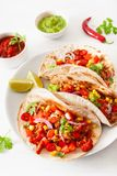 Mexican beef and pork tacos with salsa, guacamole and vegetables stock image