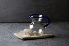 Blown glass pitcher. Mexican blown glass pitcher on grey background royalty free stock photos