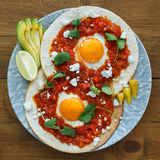 Mexican breakfast huevos rancheros: fried egg with salsa closeup in the pan Stock Image