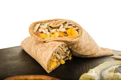 Mexican Burrito with Chicken or Beef Meat and Vegetables. Sandwich Wrap or Tortilla with Leftover Meat, Cheese Pork and Corn on Black Chopping Board Over White Royalty Free Stock Images