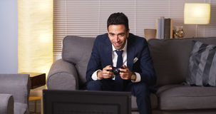 Mexican businessman playing video games. Businessman playing video games at home Royalty Free Stock Photos