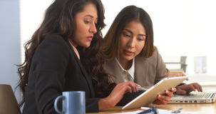 Mexican businesswoman sharing findings on tablet with Japanese colleague Stock Photo