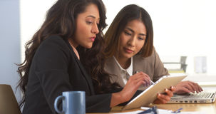 Mexican businesswoman sharing findings on tablet with Japanese colleague Royalty Free Stock Photos