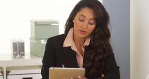 Mexican businesswoman taking notes on tablet. In the office Royalty Free Stock Photo