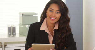 Mexican businesswoman taking notes on tablet. In the office Royalty Free Stock Photography