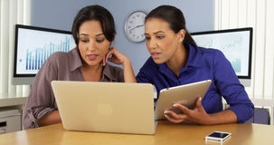 Mexican businesswomen at office desk using laptop on pad. Mexican and African American business women at office desk using laptop on pad Stock Photography