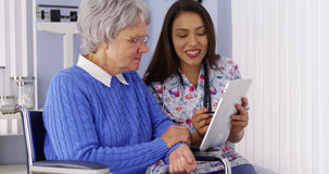 Mexican caregiver sharing tablet with elderly patient Royalty Free Stock Photos