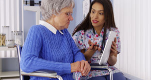 Mexican caregiver talking with tablet with senior patient stock photos