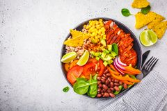 Mexican chicken burrito bowl with rice, beans, tomato, avocado,corn and spinach, top view. Mexican cuisine food concept