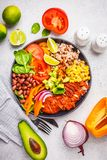 Mexican chicken burrito bowl with rice, beans, tomato, avocado,corn and spinach, top view. Mexican cuisine food concept royalty free stock photos