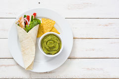 Mexican chicken fajitas with peppers lettuce and onion on a plate and white wooden background Stock Photography
