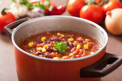 Mexican chili con carne in red rustic pot with ingredients Royalty Free Stock Image