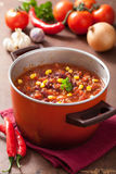 Mexican chili con carne in red rustic pot with ingredients Royalty Free Stock Photography