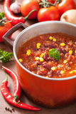 Mexican chili con carne in red rustic pot with ingredients Stock Photography