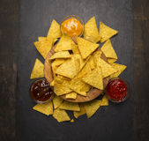 Mexican chips in a wooden bowl with cheese,ketchup, barbecue  sauce on rustic wooden background  close up top view Stock Photography