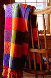 Mexican Cloth. Vibrantly coloured Mexican cloth draped over a combback chair in log home Royalty Free Stock Photos